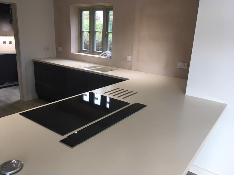 Corian Bone island and sink worktop, hot rod bars, downdraft and hob, pop up and utility room kitchen worksurfaces